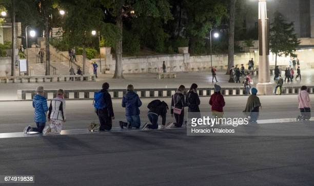 Worshippers crawl on their knees at dusk in the Sanctuary of Fatima on April 28 2017 in Fatima Portugal Thousands of pilgrims and worshippers visit...