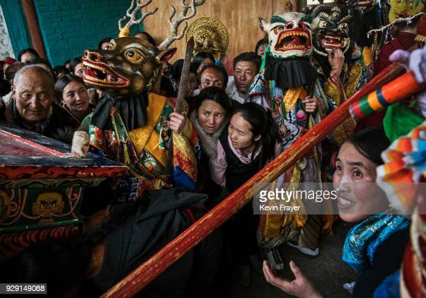 Worshippers crowd for blessings around Tibetan Buddhist Monks of the Gelug or Yellow Hat school dressed in masks for a Cham dance at the Rongwo...