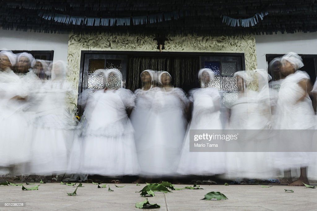 Worshippers dance and are blurred during a long exposure during a Candomble ceremony honoring goddesses Iemanja and Oxum on December 12, 2015 in Itaborai, Brazil. Candomble is an Afro-Brazilian religion whose practitioners sometimes fall into trances during ceremonies believing they have become possessed by gods, or orixas. Male worshippers are sometime possessed by female deities. The roots of the Candomble religion came to Brazil via African slaves and eventually incorporated some elements of Catholicism. Afro-Brazilian religions generally refer to Iemanja as goddess of the sea and Oxum as goddess of rivers, lakes and waterfalls, or fresh water.