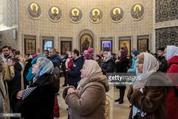Worshippers during liturgy wait to receive the eucharist at the Holy Transfiguration Cathedral which changed its affiliation from the Russian...