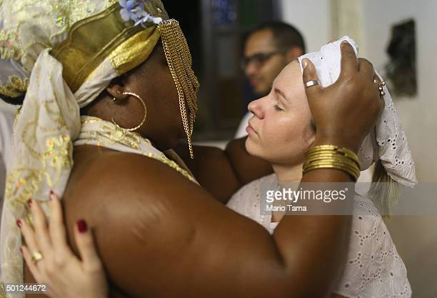 Worshippers embrace during a Candomble ceremony honoring goddesses Iemanja and Oxum on December 13 2015 in Itaborai Brazil Candomble is an...