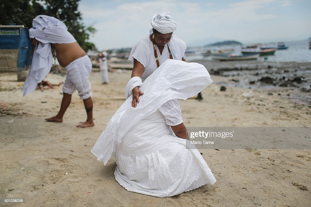 Worshippers gather along the beach on Guanabara Bay during a Candomble ceremony honoring goddesses Iemanja and Oxum on December 13, 2015 in Sao Goncalo, Brazil. Candomble is an Afro-Brazilian religion whose practitioners sometimes fall into trances during ceremonies believing they have become possessed by gods, or orixas. The roots of the Candomble religion came to Brazil via African slaves and eventually incorporated some elements of Catholicism. Afro-Brazilian religions generally refer to Iemanja as goddess of the sea and Oxum as goddess of rivers, lakes and waterfalls, or fresh water.