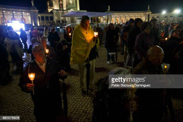 Worshippers hold candles during a night mass in the Sanctuary of Fatima on May 11 2017 in Fatima Portugal Pope Francis will be attending the...