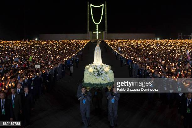 Worshippers hold candles during the Candles Lights procession as men carry a figure representing Our Lady Of Fatima at the Sanctuary of Fatima on May...
