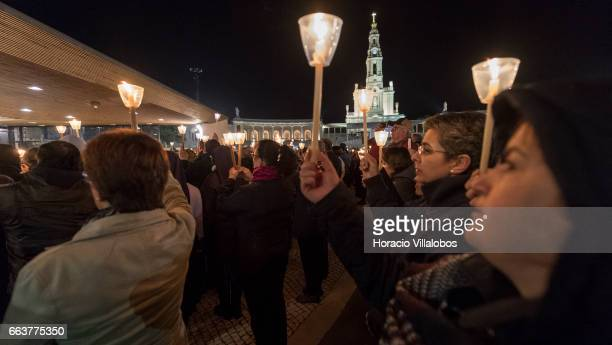 Worshippers hold candles while attending the praying of the Rosary at the Chapel of the Apparitions in Cova da Iria in the Sanctuary of Fatima on...