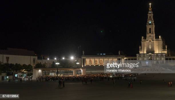 Worshippers hold candles while attending the praying of the Rosary outside the Chapel of the Apparitions in Cova da Iria in the Sanctuary of Fatima...
