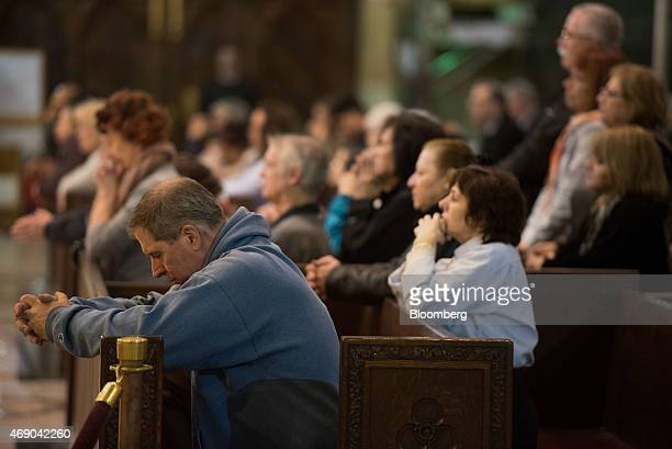 Worshippers kneel in prayer during a noon mass at Saint Patrick's Cathedral as a massive restoration effort continues in New York, U.S., on Tuesday,...