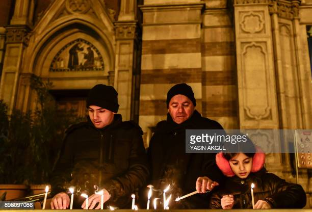 Worshippers light candles as they attend Christmas Mass at Saint Antuan Church in the Beyoglu district of Istanbul on December 24 2017 / AFP PHOTO /...