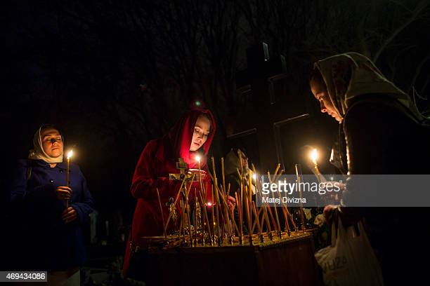 Worshippers light candles during the Orthodox Easter midnight service in front of the Orthodox Church of the Dormition at the Olsany Cemetery on...
