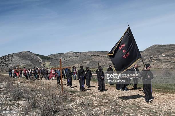 Worshippers of the brotherhood of 'La Cofadria de la Vera Cruz y El Cristo de las Lluvias' walk the way of the cross or 'Via Crucis' in Alustante on...