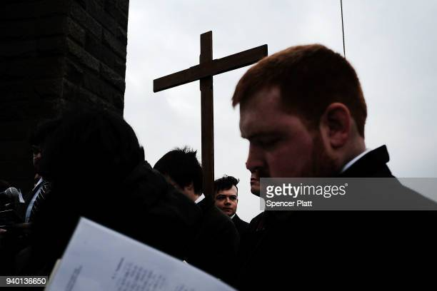 Worshippers pause at a station during the Way of the Cross procession over the Brooklyn Bridge on March 30 2018 in New York City The Way of the Cross...