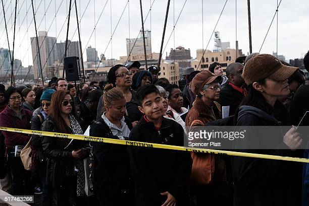 Worshippers people pause at a station during the Way of the Cross procession over the Brooklyn Bridge on March 25 2016 in New York City The Way of...
