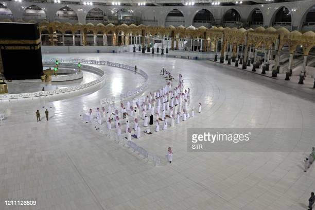 Worshippers perform Isha prayer while keeping distance between them next to the Kaaba in Mecca's Grand Mosque Islam's holiest site on April 27 2020...