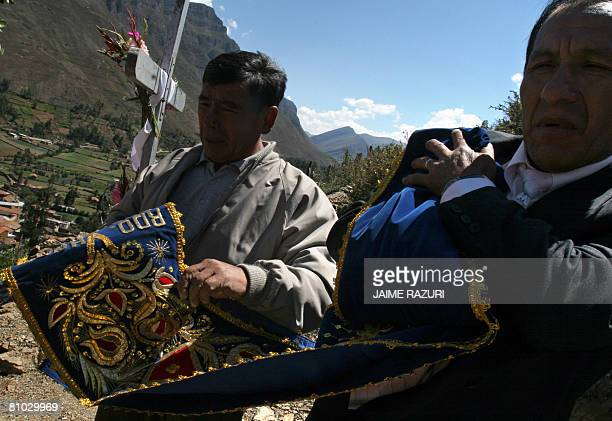 Worshippers pray as they hold a special banner to offer to a cross as part of the religious rituals worshipping the Lord of Muruhuay near the...