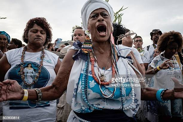 Worshippers pray as they offer their year end offerings to Iemanja the Goddess of the Sea of the AfroBrazilian religion Umbanda at Copacabana Beach...