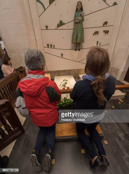 Worshippers pray before the tombs of Jacinta Marto and Lucia Santos at the Basilica of Our Lady of the Rosary in the Sanctuary of Fatima on April 1...
