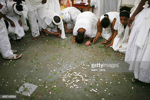 Worshippers pray during a Candomble ceremony on August 17 2014 in Cachoeira Brazil Candomble is an AfroBrazilian religion whose practitioners often...