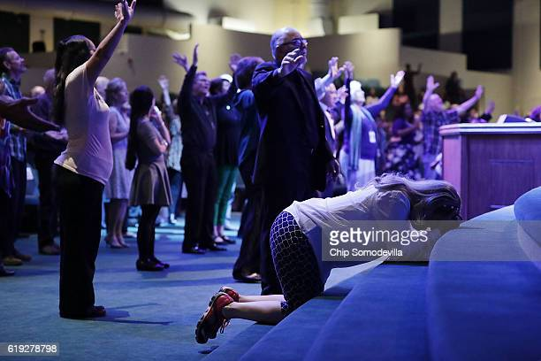 Worshippers pray during a service at the International Church of Las Vegas before the arrival of Republican presidential nominee Donald Trump October...