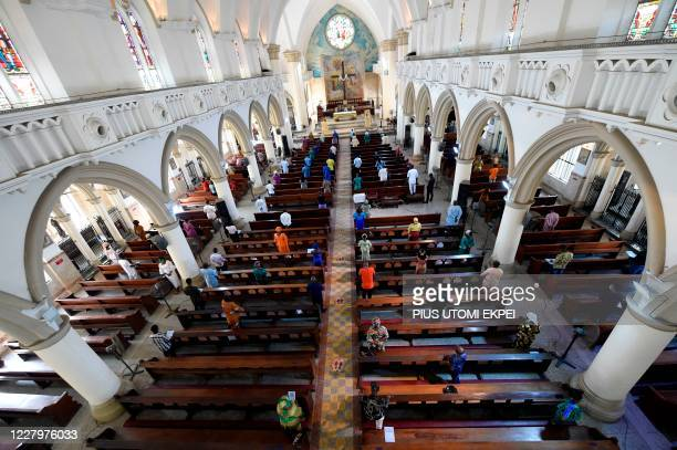 Worshippers pray in the Holy Cross Cathedral in Lagos, following the reopening of Churches and lifting of restrictions on religious gatherings by the...