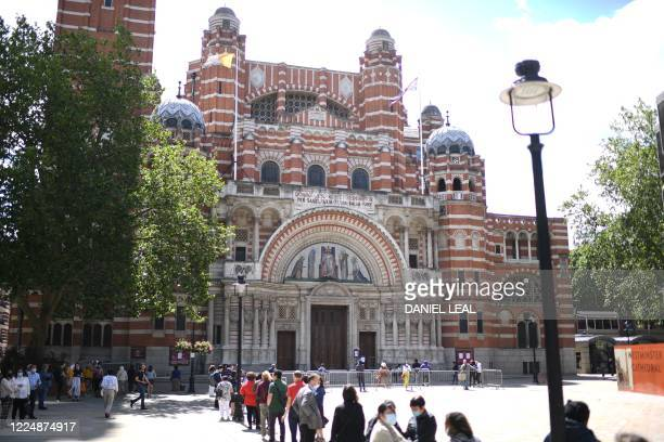 Worshippers queue to enter Westminster Cathedral in London on July 5 2020 for Sunday Mass on the first Sunday since coronavirus lockdown restrictions...