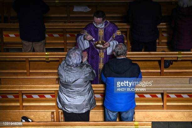Worshippers receive communion during a socially-distanced mass at St. Andrew's Cathedral in Glasgow on March 26, 2021 as churches in Scotland are...
