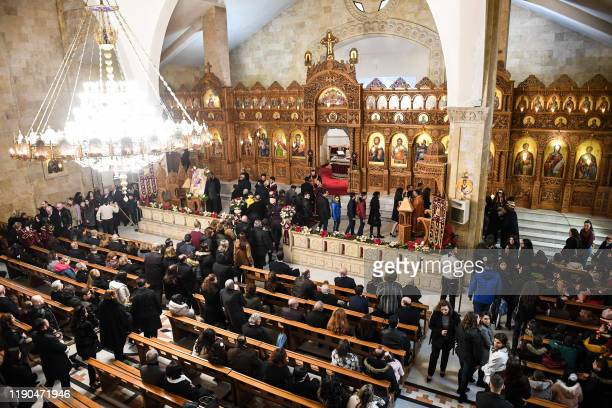 Worshippers receive communion during Christmas Morning mass at the Prophet Elias Greek Orthodox Church in Syria's northern city of Aleppo on December...