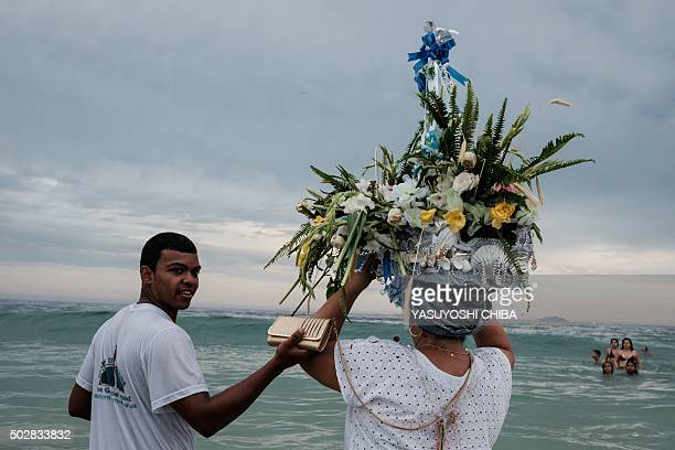 Worshippers send a handmade boat into the sea as a year end offering to Iemanja the Goddess of the Sea of the AfroBrazilian religion Umbanda at...