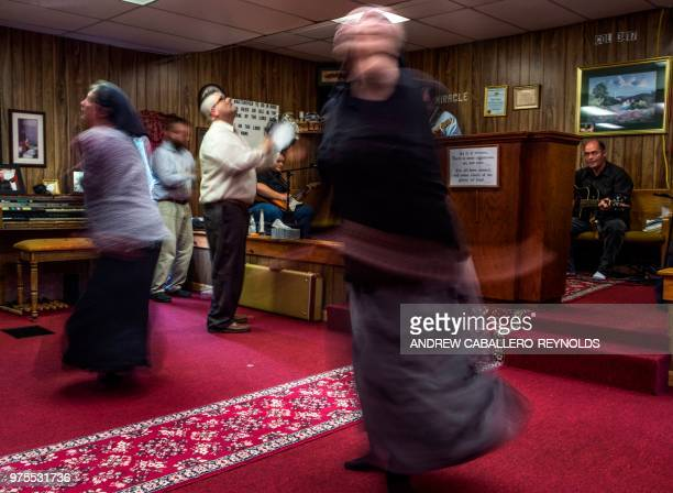 Worshippers spin in circles listening to music during a Pentecostal serpent handlers service at the House of the Lord Jesus church in Squire West...