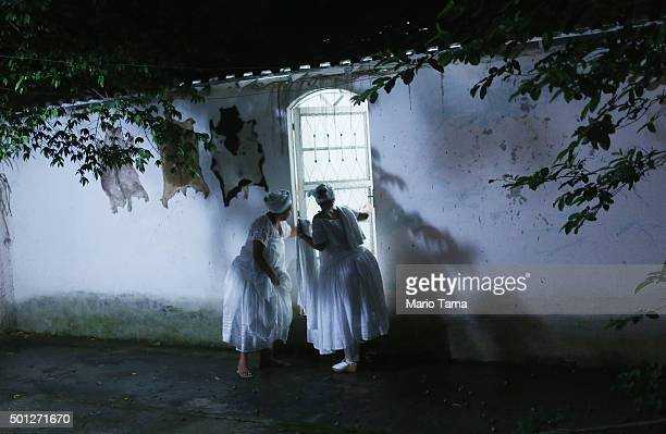 Worshippers stand outside a Candomble ceremony honoring goddesses Iemanja and Oxum on December 13 2015 in Itaborai Brazil Candomble is an...