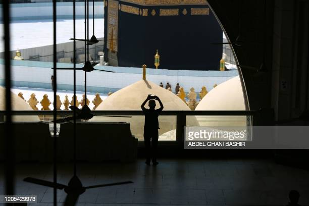 Worshippers take photographs of the Kaaba inside Mecca's Grand Mosque on March 6 a day after Saudi authorities emptied Islam's holiest site for...