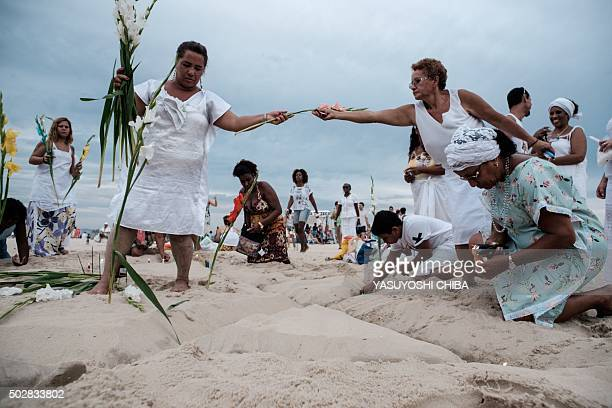 Worshippers toss flowers as year end offerings to Iemanja the Goddess of the Sea of the AfroBrazilian religion Umbanda at Copacabana Beach in Rio de...