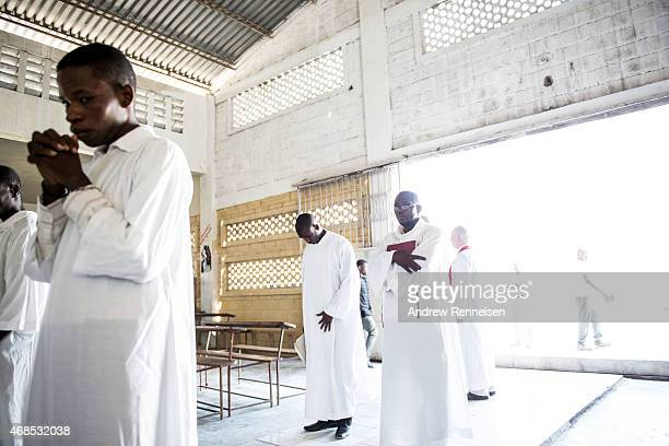 Worshippers wait to lead the procession inside St Anne's chapel before the Way of the Cross ceremony in the Cite Soleil neighborhood on April 3 2015...