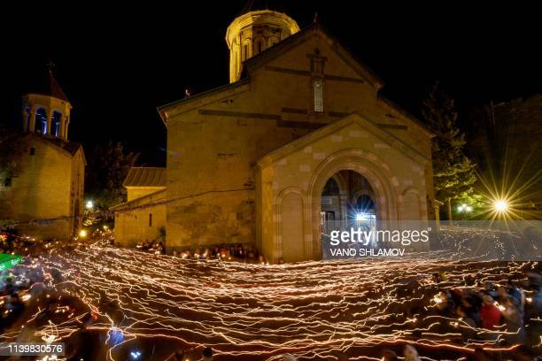 TOPSHOT Worshippers walk around the Sioni Cathedral holding lit candles during a midnight Easter service in Tbilisi early on April 28 2019