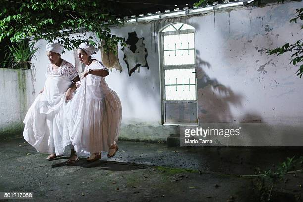 Worshippers walk during a Candomble ceremony honoring goddesses Iemanja and Oxum on December 13 2015 in Itaborai Brazil Candomble is an AfroBrazilian...