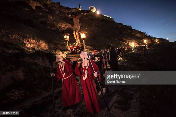 Worshippers walk the way of the cross or 'Via Crucis' during the procession of 'La Subida al Monte Calvario' in Pastrana on April 3, 2015 near...