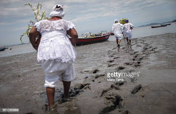 Worshippers walk with offerings to a boat on the edge of polluted Guanabara Bay during a Candomble ceremony honoring goddesses Iemanja and Oxum on...
