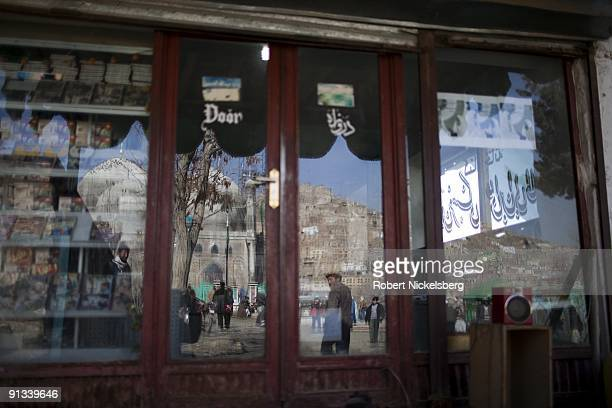 Worshippers walking to the ZiaratiSakhi shrine are reflected in a shop window in Kabul Afghanistan March 4 2009 The shrine is famous for when it is...