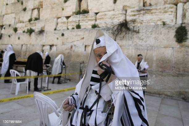 TOPSHOT Worshippers wearing the traditional Jewish prayer shawls known as Tallit pray as they keep distance of two meters between each other at the...
