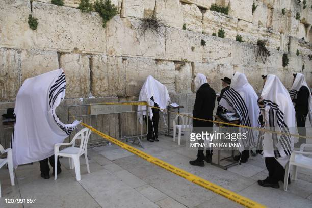 Worshippers wearing the traditional Jewish prayer shawls known as Tallit pray as they keep distance of two meters between each other at the Western...