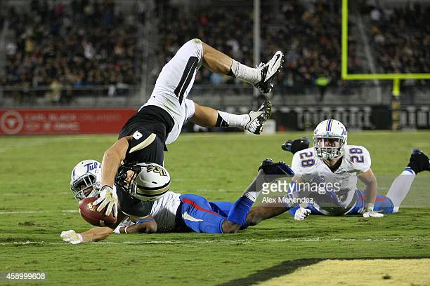 J Worton of the UCF Knights leaps for a touchdown over James Flanders of the Tulsa Golden Hurricane at Bright House Networks Stadium on November 14...