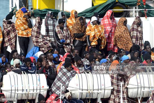 TOPSHOT Would be immigrants wait to disembark in the port of Catania on the island of Sicily on March 21 2017 from the ship 'Aquarius' following a...