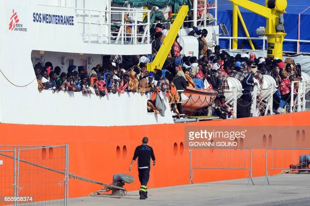 Would be immigrants wait to disembark in the port of Catania on the island of Sicily on March 21 2017 from the ship 'Aquarius' following a rescue...