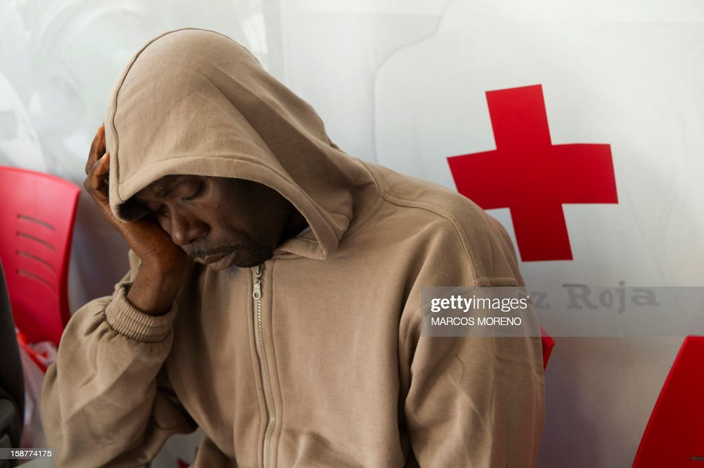 A would-be immigrant rests at a Spanish Red Cross emergency services local in Tarifa, on December 28, 2012. Spanish rescuers intercepted today a boat carrying sub-Saharan would-be immigrants, 21 men, 7 women and 4 children accross the Strait of Gibraltar. Some of them suffered from hyporthermia.