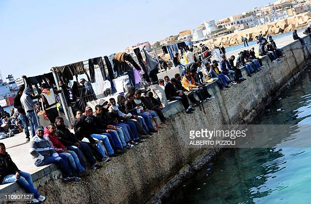 Wouldbe immigrants sit on the port of Lampedusa on March 26 2011 Italy's ports have been put on maximum alert as boats with thousands of mostly...