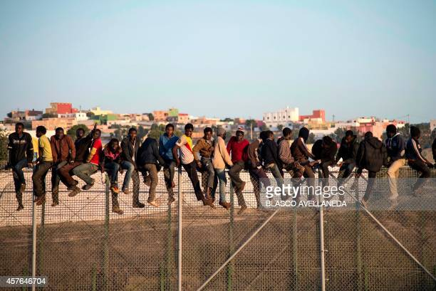 Wouldbe immigrants stand atop a boarder fence separating Morocco from the north African Spanish enclave of Melilla on October 22 following a morning...