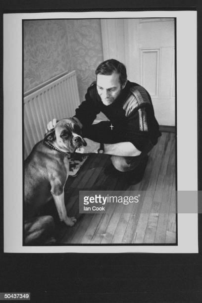 Wouldbe screenwriter Douglas Gresham son of Amer poet Joy Gresham executor of his stepdad CS Lewis's estate petting his boxer dog at home