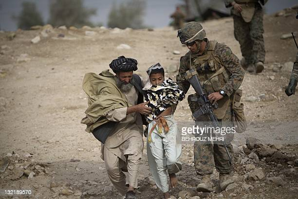 A wounded Afghan boy who was shot on his chest gets help from his father and a US Marine to get in a medevac helicopter of US Army's Task Force Lift...