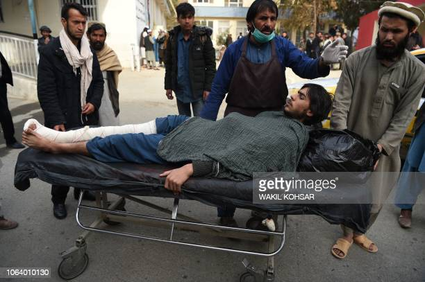 A wounded Afghan man is transferred to a local taxi after receiving treatment a day after a deadly suicide attack at a wedding hall in Kabul on...