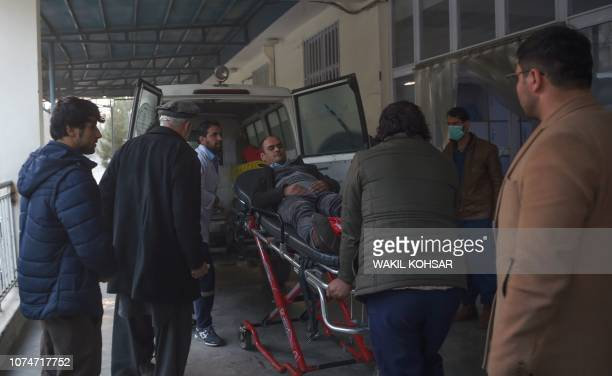A wounded Afghan man is wheeled on a stretcher at the Wazir Akbar Khan hospital after a car bomb attack in Kabul on December 24 2018 Militants...