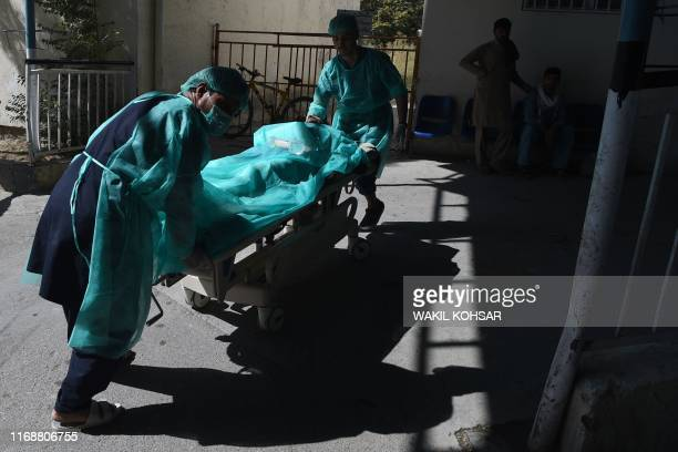 A wounded Afghan man is wheeled on a stretcher at the Wazir Akbar Khan hospital following a blast in Kabul on September 17 2019 A suicide bomber...
